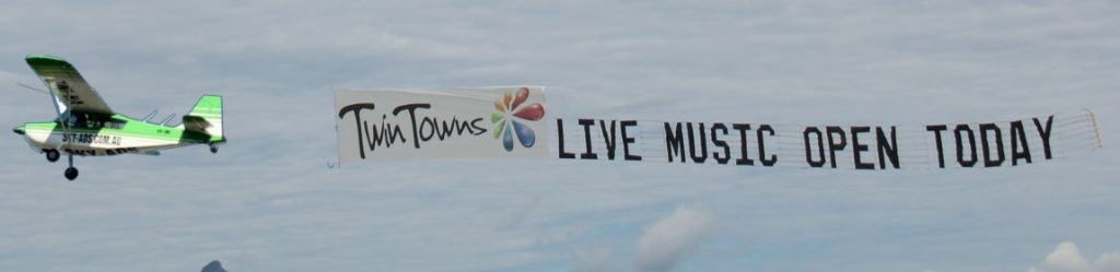 twin towns live music logo. aerial display behind aeroplane