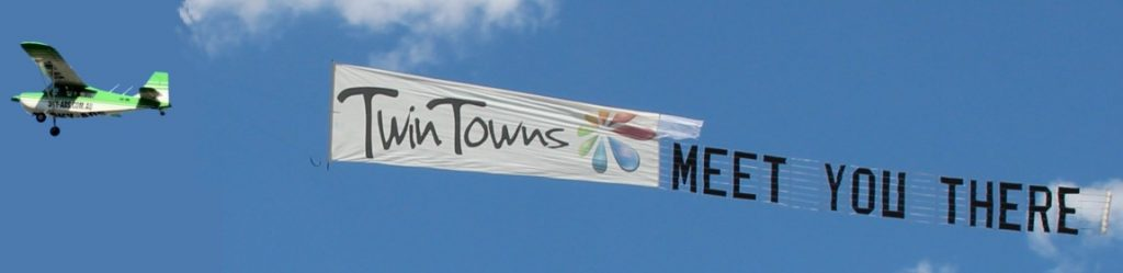 twin towns meet you there. combination logo and letters sky advertising display