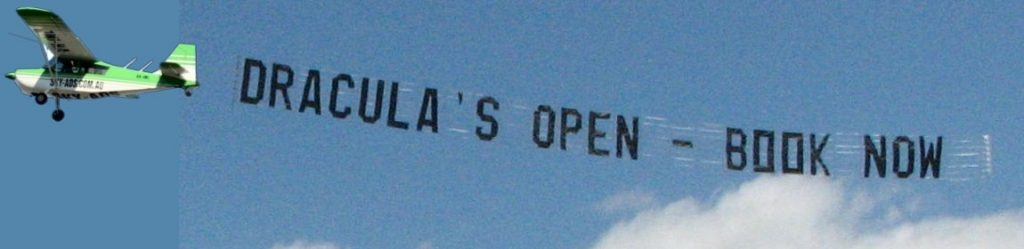 draculas airsign flying in the sky. with a white cloud in background