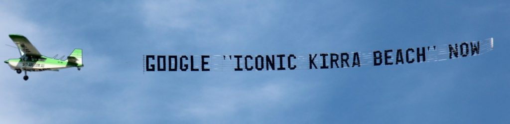 google iconic airsign flying behind aeroplane past a cloud