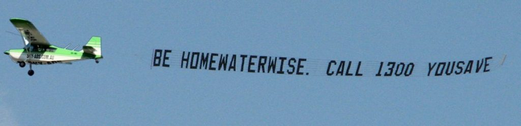 government promotion banner towing message, behind an aircraft