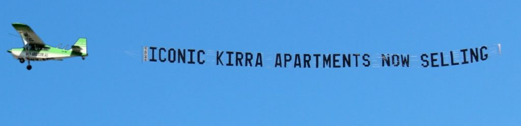 iconic apartments kirra sky-banner behind aircraft