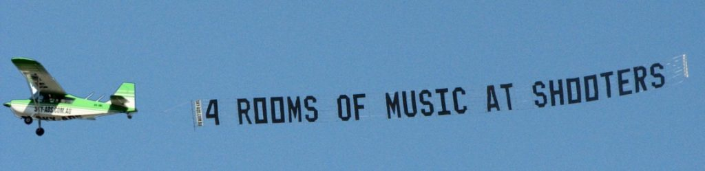 4 rooms of music at shooters. is written in aerial advertising