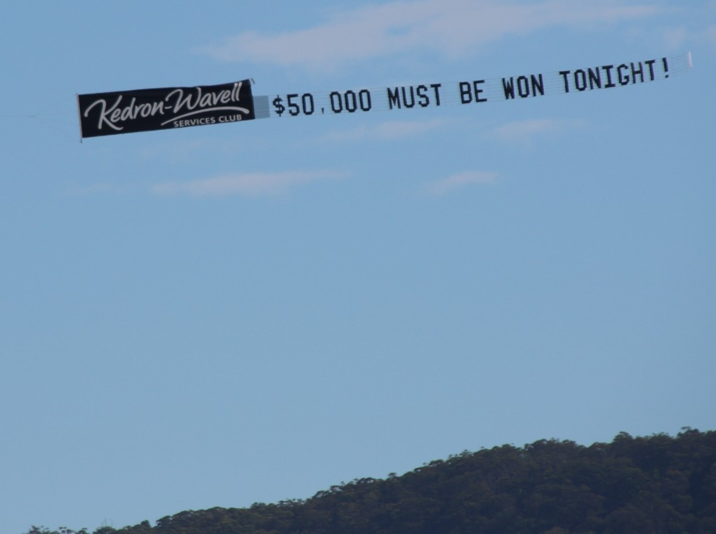 3 meter by 10 meter Logo of Kedron-wavell then words $50,000 must be won tonight. Sky Display