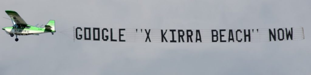 sky advertising behind a plane reads, google x kirra beach