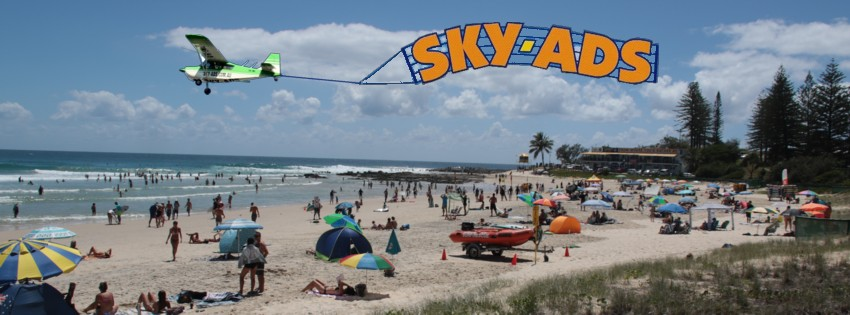 Crowded beach with SKY-ADS aircraft overhead