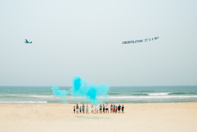"Banner flying over Beach gender reveal reads ""Congratulations it's a Boy!"""
