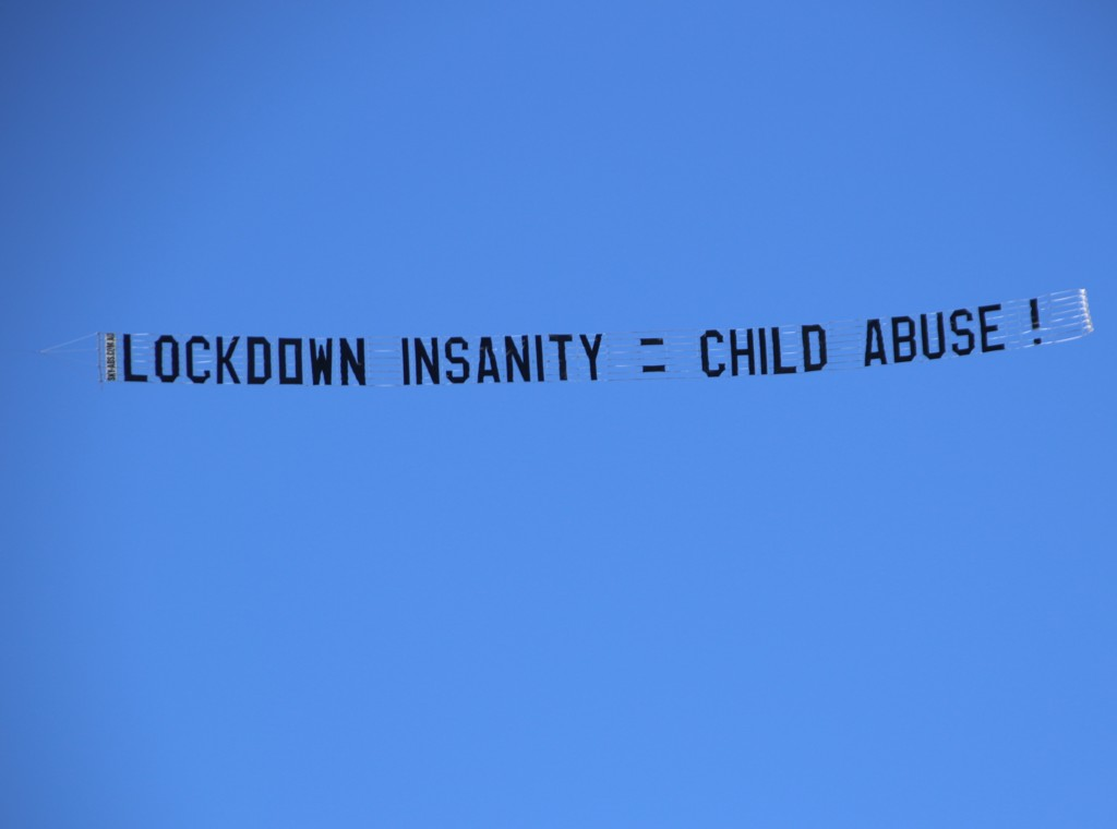 """Protest Banner Reads """"Lockdown insanity = Child Abuse"""""""