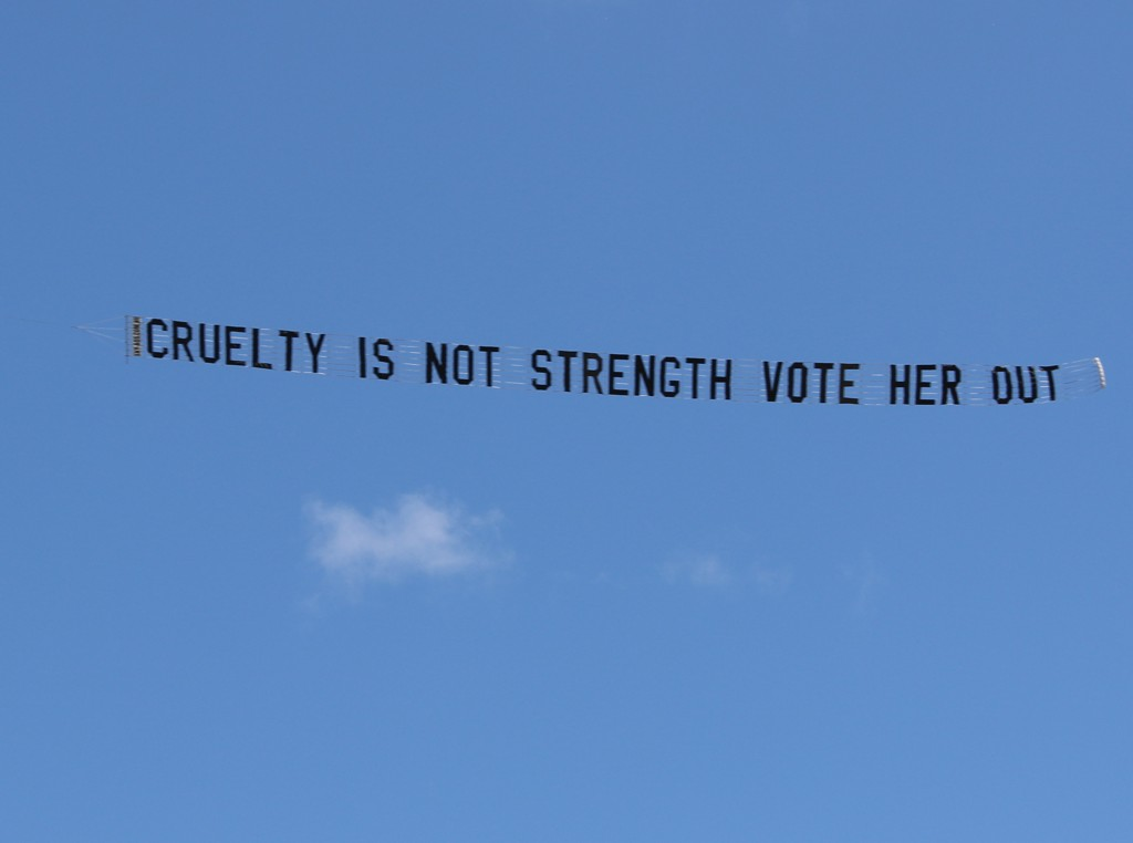"Protest Plane says ""Cruelty is not Strength, vote her out"""