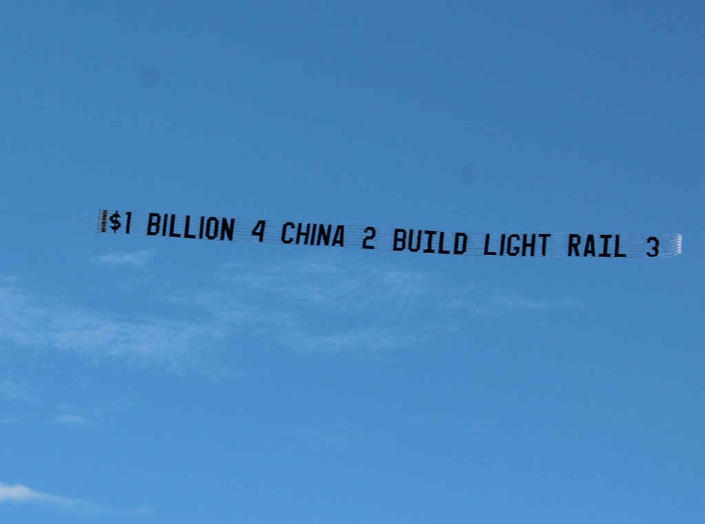 """Banner in the sky reads """"$1 Billion 4 China 2 Build Light rail 3"""""""