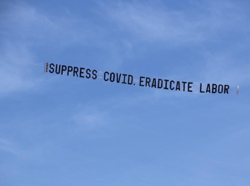 "Protest Aeroplane writes ""Suppress COVID. Eradicate Labor"