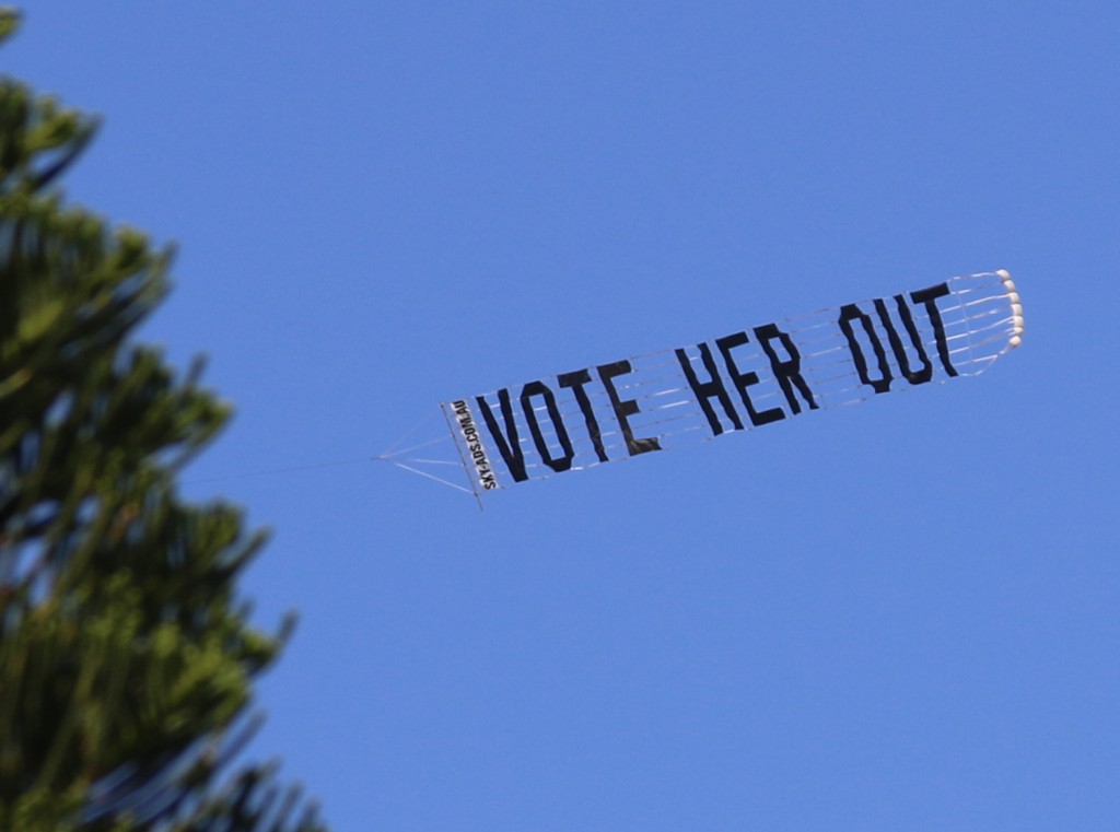 "Protest Aircraft sign reads ""Vote Her Out"""