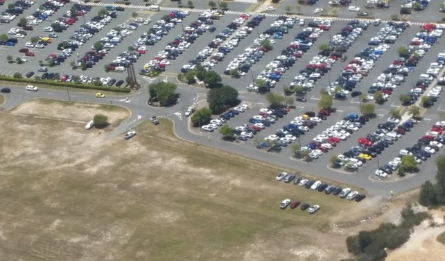 Car Park attendant directs cars onto overflow grass area because car park is full - confirming Sales Advertising Success