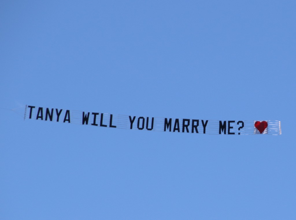"""Black banner on a blue sky reads """"Tanya will you marry me?"""""""