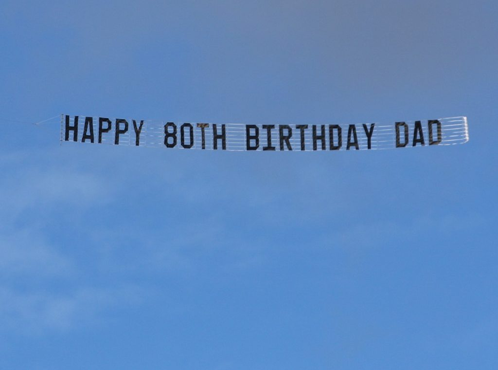 "sky banner reads ""Happy 80th Birthday DAD"""