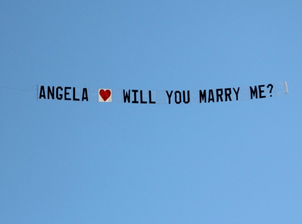 A marriage proposal written across the sky with a plane towing a banner