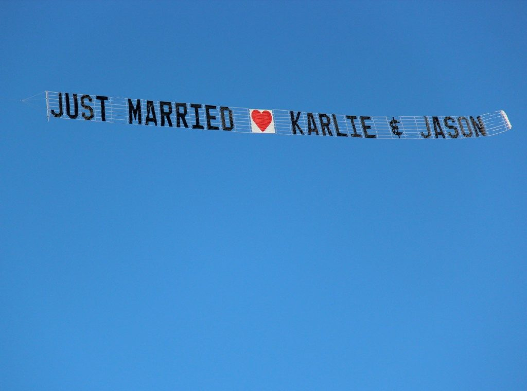 just married airsign flying in the blue sky