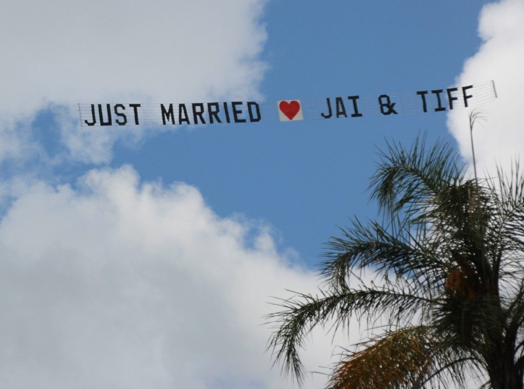 just married sky-sign FLYING PAST PALM TREE