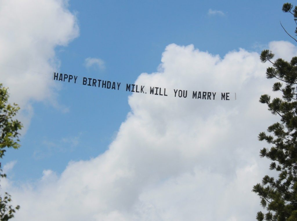 a happy birthday message written on a sky sign