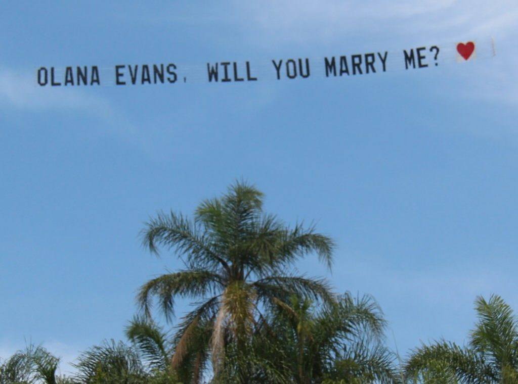 will you marry me banner. flying over a palm tree